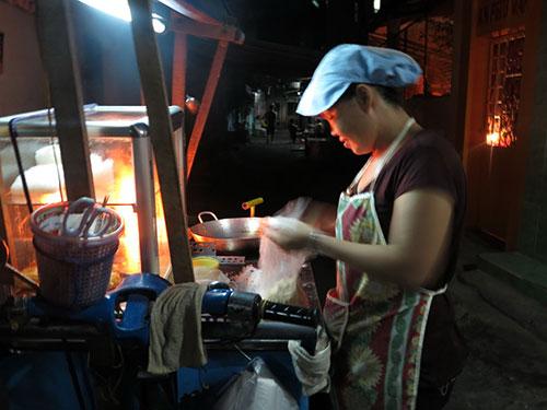 Với chiếc xe bánh tiêu, mỗi đêm, chị Nguyễn Thị Cẩm kiếm được từ 100.000-200.000 đồng Ảnh: Kha Miên