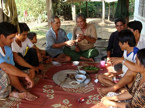 Trưởng thôn Phạm Văn Lang (người cầm ly rượu ở giữa) trong một buổi hòa giải cho  cặp vợ chồng trẻ thôn Măng Đen Ảnh: TỬ TRỰC