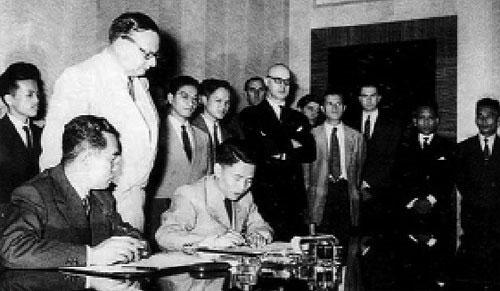 Thứ trưởng Bộ Quốc phòng Việt Nam Dân chủ Cộng hòa Tạ Quang Bửu (phải) ký hiệp định Ảnh: TƯ LIỆU