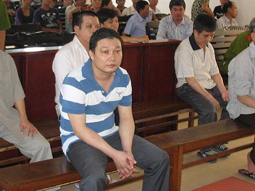 Nguyễn Thanh Bình (áo sọc) cùng đồng bọn lãnh án vì giả giấy tờ để lừa đảo và những sổ đỏ giả bị một VPCC tư ở Bình Dương phát hiện Ảnh: NHƯ PHÚ