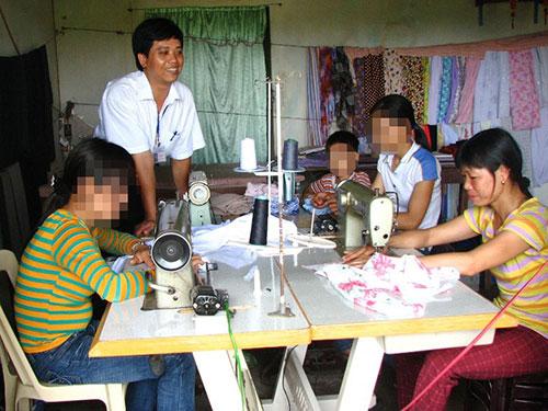 Chị Nguyễn Thị Huệ (bìa phải) tiếp cán bộ Trung tâm Y tế tỉnh Hà Nam trong hiệu may của gia đìnhẢnh: TUẤN MINH