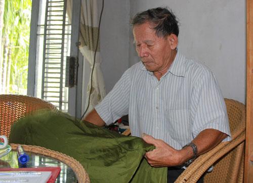 Ông Phan Văn Tư mân mê chiếc võng dù, kỷ vật thời đi B của ông