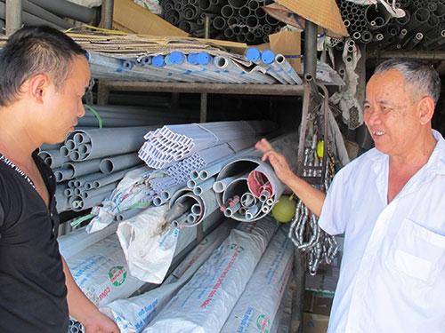 Cựu binh Trần Ngọc Thái (bìa phải) tại cơ sở kinh doanh của mình