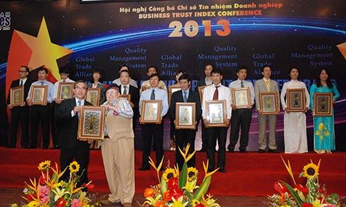 """Ông Trần Thế Lộc (bên trái),giám đốc điều hành, đại diện Manulife Việt Nam nhận biểu tượng""""Doanhnghiệp phát triển bền vững năm 2013"""""""