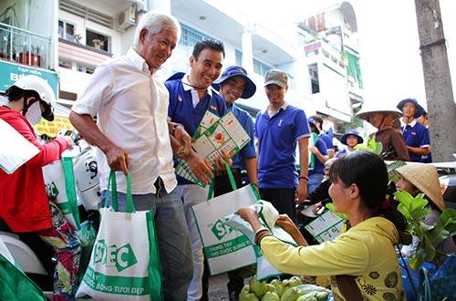 Đại sứ chương trình Quyền Linh đang phát tờ rơi và túi sinh học cho người dân