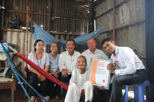 Tổng Giám đốc Tổ chức Kỷ lục châu Á Biswaroop Roy Chowhury trao bằng xác lập kỷ lục Cụ bà cao tuổi nhất châu Á cho cụ Nguyễn Thị Trù (121 tuổi). (Ảnh do VietKings cung cấp)