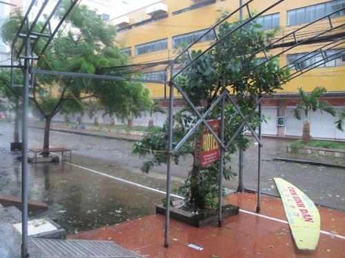 Một biển hiệu bị gió bão thổi bay trên đường phố Móng Cái