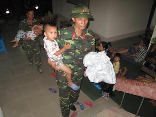 Bộ đội bế các cháu nhỏ, có cháu còn đang ngủ, di chuyên tới nơi trú ẩn an toàn