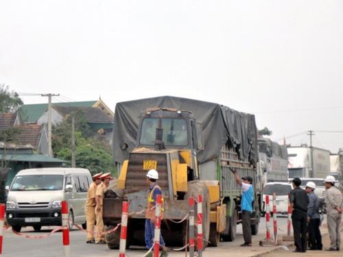 Lực lượng chức năng đang tìm cách đưa chiếc xe tải hỏng vào bên đường để giải tỏa ách tắc