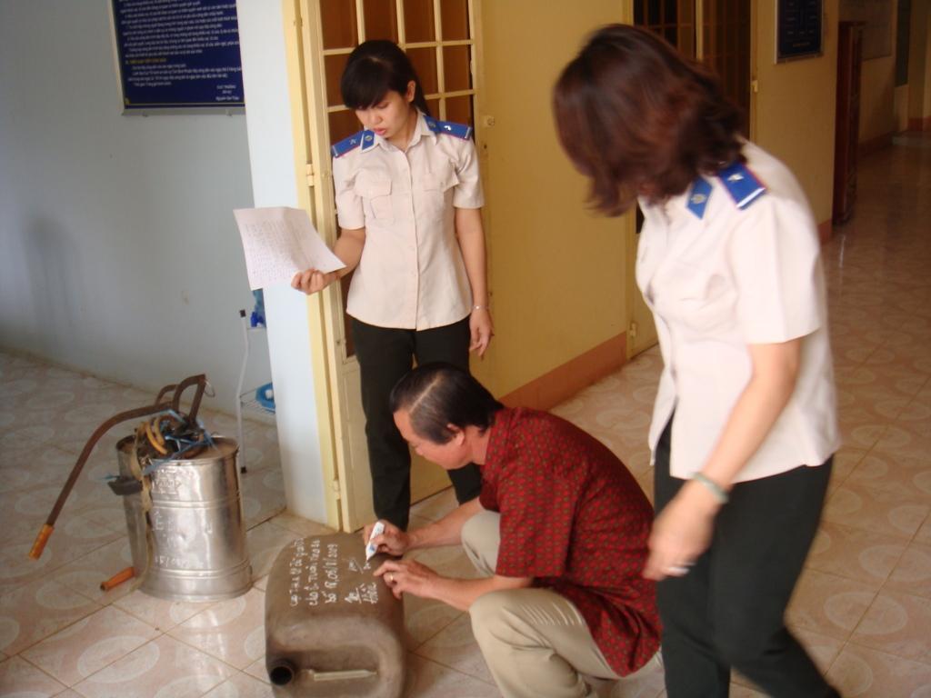 """Ông Dương Bá Tuân đang ký vào can nhựa là """"vật chứng"""" để bảo đảm sau này Cục THADS tỉnh Bình Phước và ông Tuân không gặp rắc rối, và có chứng tích giao nhận."""