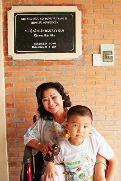 NSND Kim Cương và cháu nội trước lớp dạy vi tính cho trẻ em mồ côi, khuyết tật mang tên NSND Bảy Nam