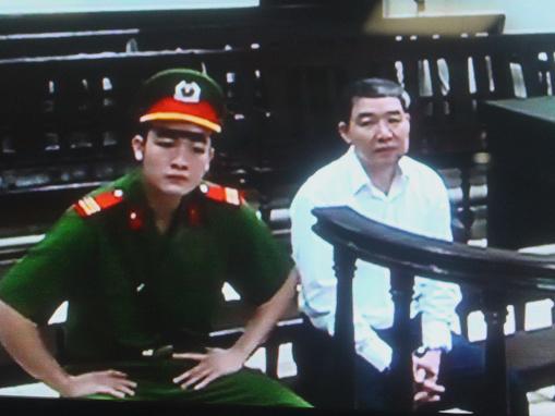 Bị cáo Dương Chí Dũng trông vẻ thẫn thờ ngồi chờ bắt đầu phiên xét xử ngày 24-4 - Ảnh chụp qua màn hình
