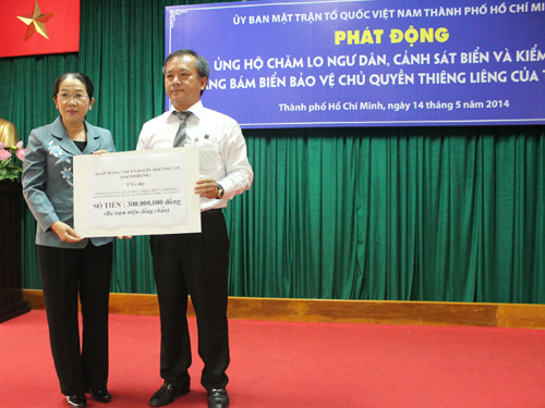 """Ông Phan Đình Tuệ, Phó Tổng giám đốc kiêm Chủ tịch Công đoàn  Sacombank (bên phải) trao tiền ủng hộ cho đại diện Quỹ """"Vì Trường Sa thân yêu, vì tuyến đầu Tổ quốc"""""""