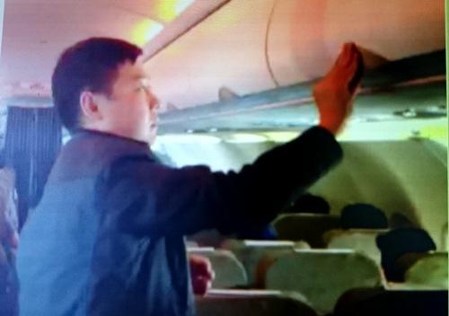 Hình ảnh về cảnh hành khách Zhang Giang (Trung Quốc) ăn cắp đồ tại giá hành lý trên chuyến bay VN 600 Bangkok (Thái Lan) - TP HCM chiều 19-1 - Ảnh cắt từ clip do tiếp viên quay được