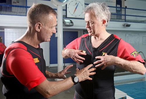 Nelson (trái) hướng dẫn sử dụng áo phao trong tập trị liệu hồi phục chức năng cơ thể