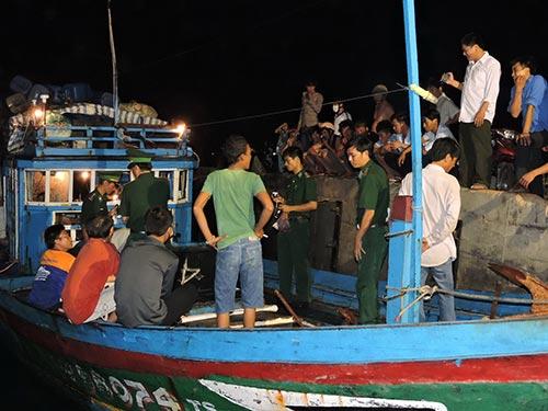 Cơ quan chức năng đến ghi nhận việc tàu cá QNg 66074 TS bị đập phá, cướp tài sản tối ngày 15-8 - Ảnh: V. Mịnh