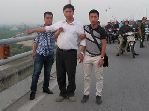 Bác sĩ Nguyễn Mạnh Tường (áo sơmi trắng) chỉ nơi ném nạn nhân Lê Thị Thanh Huyền từ trên cầu Thanh Trì xuống sông Hồng để phi tang