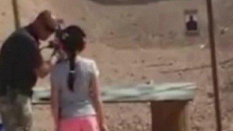 Anh Charles Vacca hướng dẫn bé gái 9 tuổi sử dụng súng. Ảnh: BBC