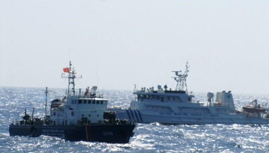 Tàu hải cảnh Trung Quốc (trái) hung hăng vây ép và phun vòi rồng vào tàu kiểm ngư Việt Nam (phải)