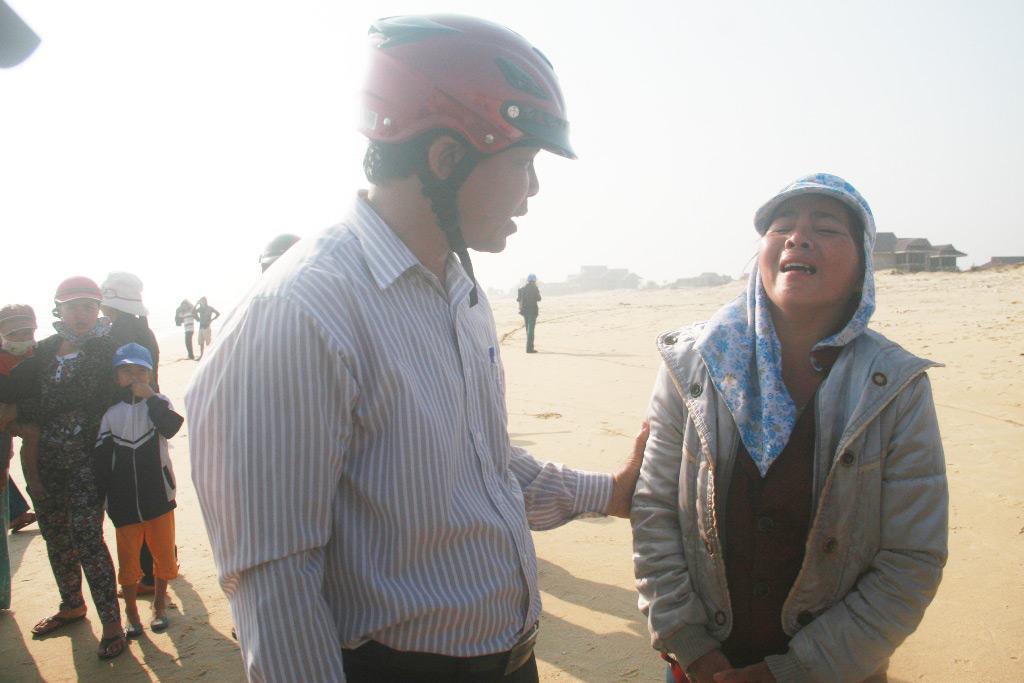 Ông Nguyễn Giúp, Chủ tịch xã Tam Tiến động viên tinh thần bà Huỳnh Thị Hoa khi nhìn thấy chị gái bị sóng cuốn mà không cứu được