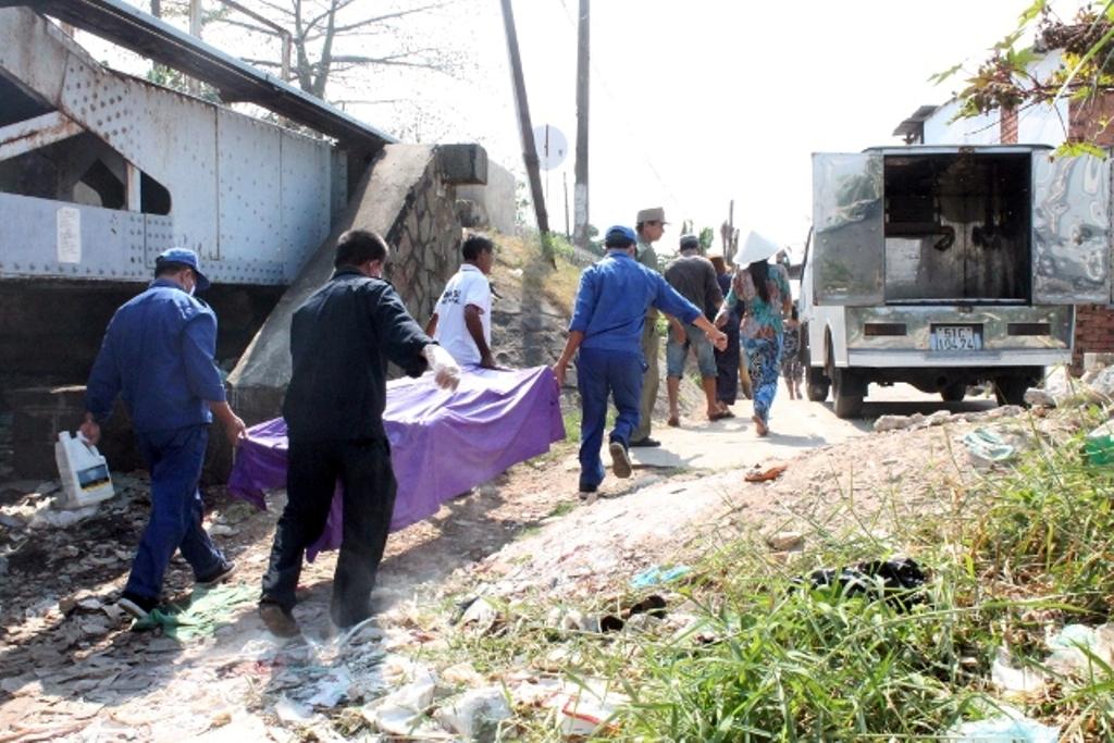 Xác nạn nhân được chuyển lên xe đưa về nhà xác khám nghiệm tử thi