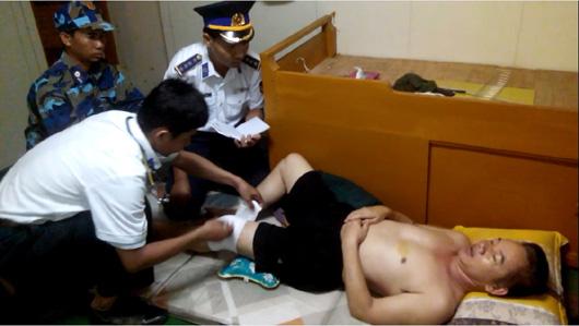Cảnh sát biển đang chăm sóc thuyền viên bị cướp biển tấn công bị thương