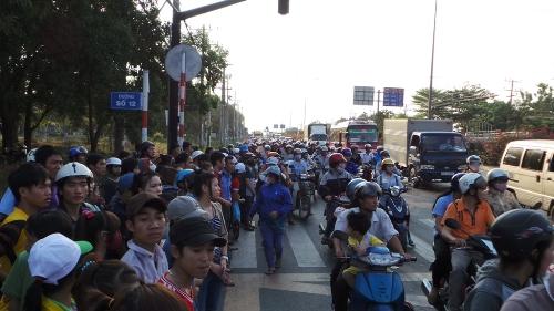 Người đi đường và hàng trăm công nhân tan ca đổ ra đường đứng xem tai nạn khiến giao thông qua đây gặp nhiều khó khăn