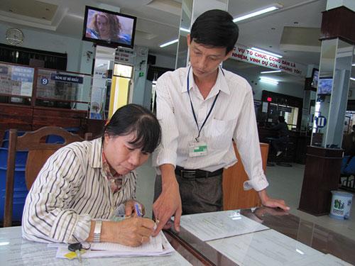 Cán bộ công chức quận Thanh khê, TP Đà Nẵng hướng dẫn người dân đến làm giấy tờ  Ảnh: HOÀNG DŨNG
