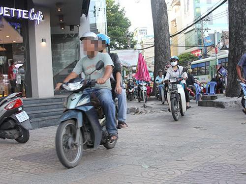 Leo vỉa hè trong khi dừng chờ đèn đỏ là chuyện diễn ra thường xuyên đến mức trở thành bình thường.  Ảnh chụp tại giao lộ Cao Thắng - Nguyễn Thị Minh Khai (quận 3, TP HCM)Ảnh: Sỹ Đông