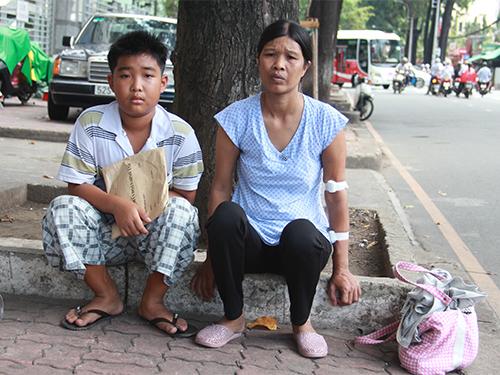 Hai mẹ con chị Đoàn Thị Rõ chờ lấy thuốc ở bên ngoài Bệnh viện Nhi Đồng 2