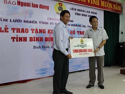 Ông Đỗ Danh Phương, Tổng Biên tập Báo Người Lao Động (phải), trao biển tượng trưng 1 tỉ đồng ủng hộ ngư dân tỉnh Bình Định