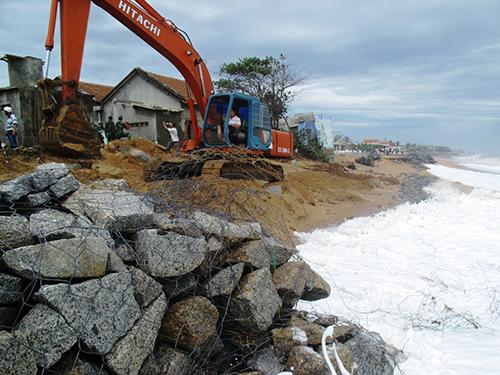 Người dân cho rằng bờ kè vừa được xây dựng đã bị biển nuốt chửng là do doanh nghiệp hút cát ở cửa sông