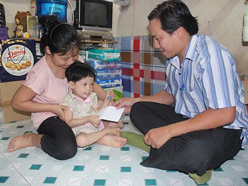 Phóng viên Báo Người Lao Động trao tiền của bạn đọc giúp đỡ cháu Đặng Bảo Ngọc