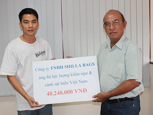 Đại diện Công ty Shilla Bags Việt Nam (trái) trao tiền ủng hộ cho Quỹ Tấm lòng vàng Người Lao Động Ảnh: Trường Hoàng