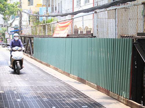 Cầu trên đường Phan Văn Hân được chính quyền địa phương dùng lưới B40 và tôn rào kín để ngăn người dân thải rác xuống kênh