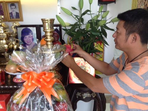 Tấn Beo chuẩn bị hoa quả cúng trên bàn thờ cha