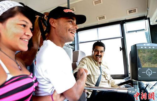 Tổng thống Venezuela Nicolas Maduro thân thiện bắt tay hành khách khi lái xe buýt  trong chiến dịch tranh cử hồi tháng 3. Ảnh China News