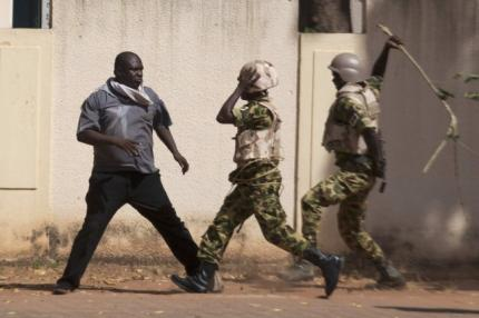 Binh lính chính phủ vung gậy trước người biểu tình ở thủ đô Ouagadougou. Ảnh: Reuters