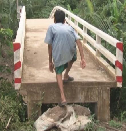 Một cây cầu nông thôn ở xã An Thạnh Tây do mố cầu quá cao gây khó khăn cho việc đi lại của người dân.