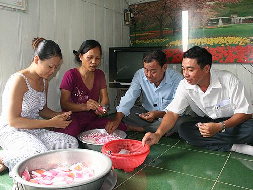 Ông Ngô Ngọc Tấn, Trưởng Chi nhánh CEP quận 8 - TPHCM (phải), thăm hỏi tình hình làm ăn của bà con nghèo
