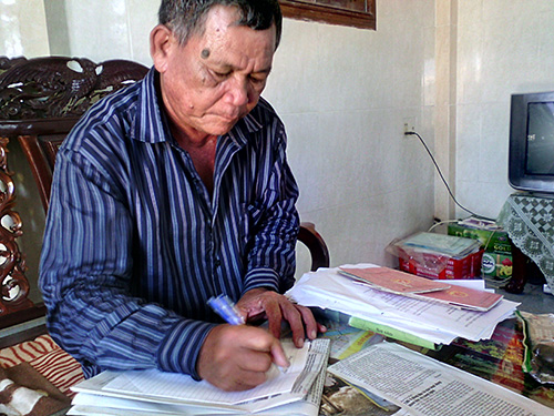 Ông Võ Văn Kèn - Trưởng thôn Lại Tân, xã Phú Mậu, huyện Phú Vang, tỉnh Thừa Thiên - Huế - giúp dân làm giấy tờ  Ảnh:  QUANG NHẬT