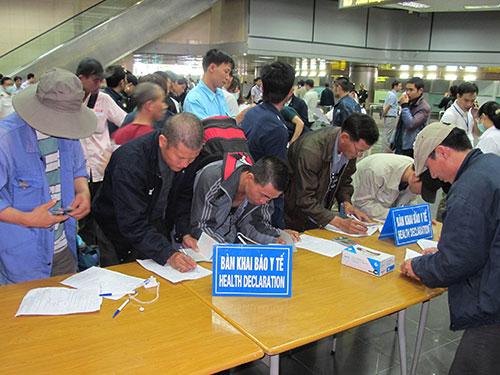 Hành khách đến từ vùng có dịch khai báo y tế tại sân bay quốc tế Nội Bài trước khi nhập cảnh