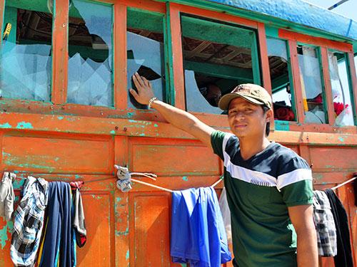 Ngư dân Võ Bá Nha (tỉnh Quảng Ngãi) bên chiếc tàu vỏ gỗ bị tàu Trung Quốc đâm hỏng ca bin hồi cuối tháng 5-2014.Ảnh: Tử Trực