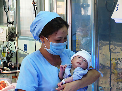 Bé Nguyễn Quốc Huy trong vòng tay của một điều dưỡng viên Bệnh viện Nhi Đồng 1