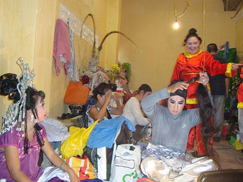 Nghệ sĩ hát bội ngồi bệt trong một góc đình hóa trang, chuẩn bị ra sân khấu biểu diễn