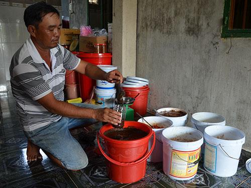 Ông Huỳnh Thanh Hải đang chiết mắm còng vào hũ