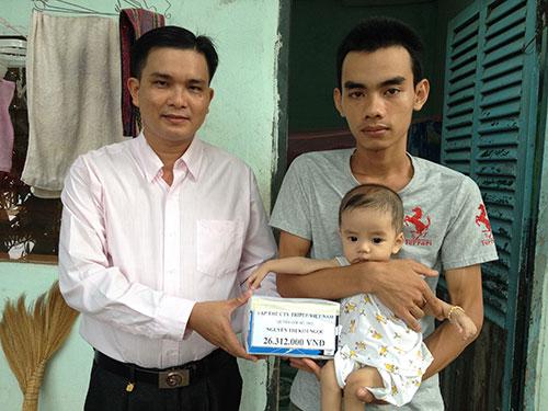 Ông Lê Trần Thanh Hải (bìa trái), Chủ tịch Công đoàn Công ty TNHH Triple Việt Nam, trao tiền hỗ trợ gia đình chị Nguyễn Thị Kim Ngọc