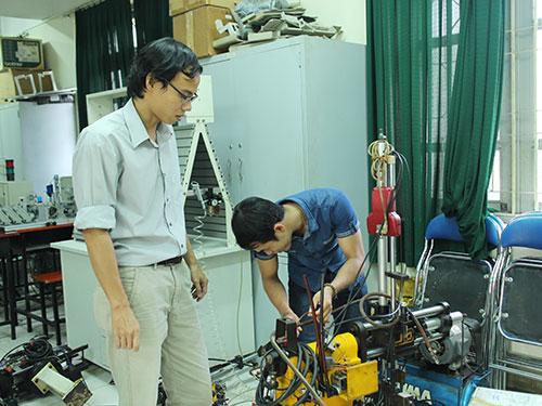 Đặng Trung Nam (bìa trái), giảng viên Khoa Cơ khí Công nghệ Trường ĐH Nông Lâm TP HCM, hướng dẫn sinh viên thực hành