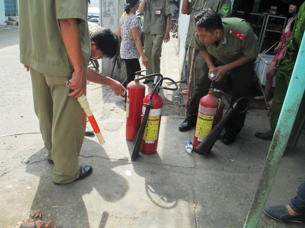 Lực lượng chức năng chuẩn bị bình chữa cháy để cứu hỏa khi hung thủ dọa cho nổ bình gas