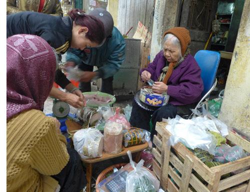 Cụ bà gốc làng Ước Lễ (nổi tiếng với nghề truyền thống làm giò chả ở Hà Nội) bán bánh chưng trên phố Hàng Đồng